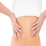 Close-up mid section of a young woman suffering from back pain over white background